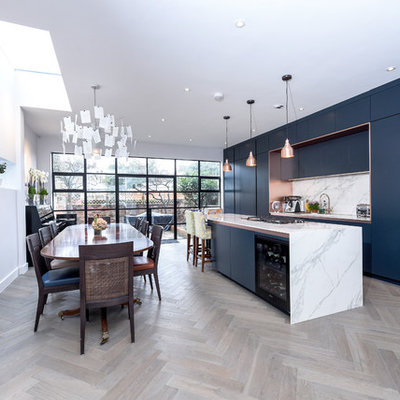 Eat-in kitchen - mid-sized contemporary single-wall light wood floor and beige floor eat-in kitchen idea in London with flat-panel cabinets, blue cabinets, marble countertops, white backsplash, marble backsplash, an island and white countertops