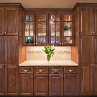 Idéer för ett mellanstort klassiskt beige kök, med en undermonterad diskho, luckor med upphöjd panel, bänkskiva i kvarts, beige stänkskydd, stänkskydd i tunnelbanekakel, rostfria vitvaror, vinylgolv, en köksö, brunt golv och skåp i mörkt trä