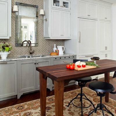 Large elegant medium tone wood floor enclosed kitchen photo in Atlanta with recessed-panel cabinets, gray cabinets, paneled appliances, an undermount sink, marble countertops, gray backsplash, subway tile backsplash and an island