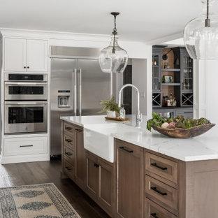 シカゴの広いカントリー風おしゃれなキッチン (エプロンフロントシンク、シェーカースタイル扉のキャビネット、白いキャビネット、クオーツストーンカウンター、白いキッチンパネル、ガラスまたは窓のキッチンパネル、シルバーの調理設備、無垢フローリング、茶色い床、白いキッチンカウンター) の写真