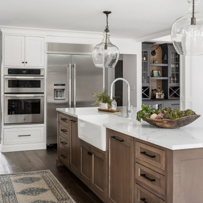 Open concept kitchen - large country l-shaped medium tone wood floor and brown floor open concept kitchen idea in Chicago with a farmhouse sink, shaker cabinets, white cabinets, quartz countertops, white backsplash, window backsplash, stainless steel appliances, an island and white countertops