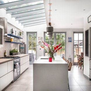 This is an example of a traditional galley kitchen/diner in London with a submerged sink, flat-panel cabinets, grey cabinets, white splashback, metro tiled splashback, integrated appliances, an island and grey floors.