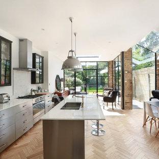 Große Moderne Wohnküche mit Doppelwaschbecken, Marmor-Arbeitsplatte, Küchenrückwand in Weiß, Rückwand aus Marmor, Küchengeräten aus Edelstahl, hellem Holzboden, beigem Boden, Glasfronten, schwarzen Schränken und Kücheninsel in London