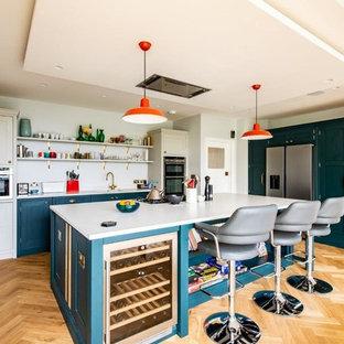 Imagen de cocina clásica renovada con armarios estilo shaker, puertas de armario turquesas, salpicadero blanco, electrodomésticos de acero inoxidable, suelo de madera clara, una isla, suelo beige y encimeras blancas