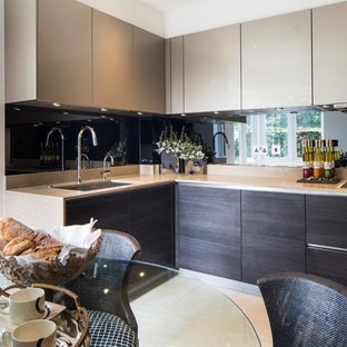Design ideas for a medium sized modern u-shaped kitchen/diner in London with a built-in sink, flat-panel cabinets, dark wood cabinets, granite worktops, black splashback, glass sheet splashback, porcelain flooring and no island.