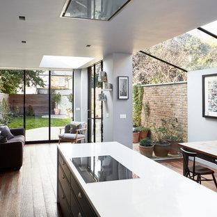 Idéer för stora funkis linjära vitt kök med öppen planlösning, med en rustik diskho, blå skåp, bänkskiva i kvartsit, vitt stänkskydd, mörkt trägolv, en köksö, skåp i shakerstil, stänkskydd i cementkakel och integrerade vitvaror