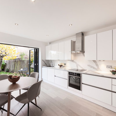 Example of a minimalist single-wall eat-in kitchen design in London with flat-panel cabinets, white cabinets, stainless steel appliances, no island and white countertops