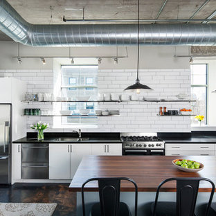 Large industrial eat-in kitchen appliance - Inspiration for a large industrial single-wall concrete floor eat-in kitchen remodel in Minneapolis with flat-panel cabinets, white cabinets, white backsplash, subway tile backsplash, an island, a double-bowl sink, granite countertops and stainless steel appliances