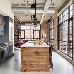 Industrial open concept kitchen ideas - Inspiration for an industrial galley gray floor open concept kitchen remodel in Minneapolis with gray cabinets, stainless steel appliances, white countertops, an undermount sink, flat-panel cabinets, white backsplash and an island