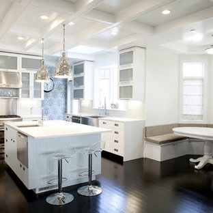 Inspiration for a mid-sized transitional l-shaped eat-in kitchen in San Francisco with stainless steel appliances, glass-front cabinets, white cabinets, white splashback, subway tile splashback, dark hardwood floors, with island, brown floor and a farmhouse sink.