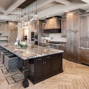 フェニックスのサンタフェスタイルのおしゃれなアイランドキッチン (エプロンフロントシンク、シェーカースタイル扉のキャビネット、ヴィンテージ仕上げキャビネット、マルチカラーのキッチンパネル、シルバーの調理設備、ベージュの床、マルチカラーのキッチンカウンター) の写真