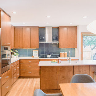 Mid-sized midcentury modern eat-in kitchen designs - Example of a mid-sized midcentury modern l-shaped light wood floor eat-in kitchen design in Grand Rapids with an undermount sink, flat-panel cabinets, medium tone wood cabinets, quartz countertops, blue backsplash, paneled appliances, an island and white countertops