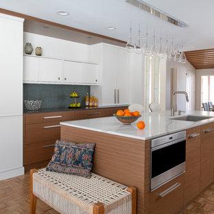 Idéer för mellanstora retro vitt kök, med en enkel diskho, släta luckor, skåp i mellenmörkt trä, bänkskiva i kvarts, grönt stänkskydd, rostfria vitvaror, mellanmörkt trägolv, en köksö och brunt golv