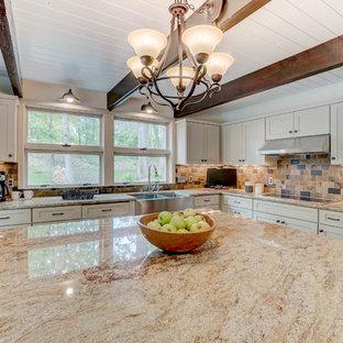 ミネアポリスの中サイズのミッドセンチュリースタイルのおしゃれなキッチン (エプロンフロントシンク、落し込みパネル扉のキャビネット、ベージュのキャビネット、御影石カウンター、マルチカラーのキッチンパネル、セラミックタイルのキッチンパネル、シルバーの調理設備の、セラミックタイルの床、マルチカラーの床、ベージュのキッチンカウンター) の写真