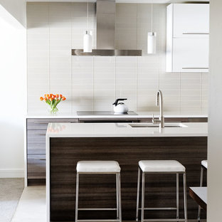 Mid-sized modern kitchen designs - Kitchen - mid-sized modern galley porcelain tile kitchen idea in Denver with flat-panel cabinets, white backsplash, an undermount sink, solid surface countertops, stainless steel appliances, an island, glass tile backsplash and dark wood cabinets