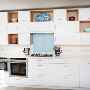 Inspiration for a small modern single-wall kitchen/diner in Oxfordshire with flat-panel cabinets, white cabinets and granite worktops.
