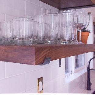 Immagine di una cucina moderna di medie dimensioni con lavello sottopiano, ante in stile shaker, ante nere, top in superficie solida, paraspruzzi bianco, paraspruzzi con piastrelle diamantate, elettrodomestici in acciaio inossidabile e pavimento in gres porcellanato