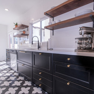 Inredning av ett modernt mellanstort kök med öppen planlösning, med en undermonterad diskho, skåp i shakerstil, svarta skåp, bänkskiva i koppar, vitt stänkskydd, stänkskydd i tunnelbanekakel, rostfria vitvaror och klinkergolv i porslin