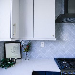 サンディエゴの中くらいのモダンスタイルのおしゃれなキッチン (アンダーカウンターシンク、フラットパネル扉のキャビネット、青いキャビネット、クオーツストーンカウンター、グレーのキッチンパネル、セラミックタイルのキッチンパネル、黒い調理設備、クッションフロア、グレーの床、白いキッチンカウンター) の写真