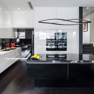 Photo of a large contemporary kitchen in Perth with granite benchtops, black splashback, glass sheet splashback, black appliances, porcelain floors, with island and white benchtop.