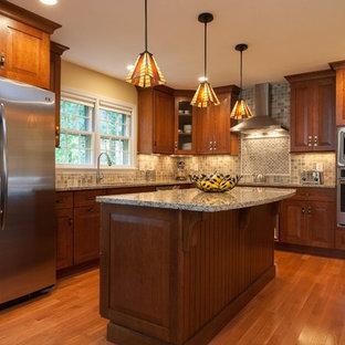 Exempel på ett mellanstort amerikanskt l-kök, med luckor med upphöjd panel, skåp i mellenmörkt trä, stänkskydd i stenkakel, rostfria vitvaror, en undermonterad diskho, granitbänkskiva, flerfärgad stänkskydd, mellanmörkt trägolv och en köksö