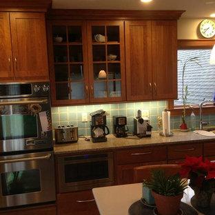 Diseño de cocina comedor lineal, actual, de tamaño medio, con fregadero bajoencimera, armarios estilo shaker, puertas de armario marrones, encimera de cuarzo compacto, salpicadero gris, salpicadero de azulejos de terracota, electrodomésticos de acero inoxidable, suelo de terrazo, una isla y suelo rojo