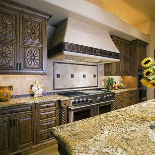 Offene, Einzeilige, Große Mediterrane Küche mit Unterbauwaschbecken, profilierten Schrankfronten, dunklen Holzschränken, Granit-Arbeitsplatte, Küchenrückwand in Beige, Rückwand aus Travertin, Küchengeräten aus Edelstahl, Betonboden, zwei Kücheninseln und buntem Boden in Phoenix