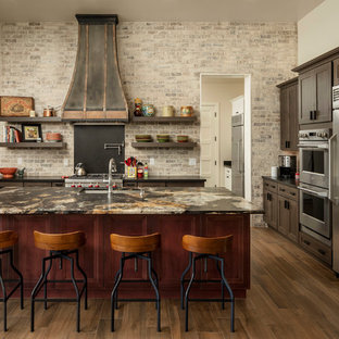 Large southwestern enclosed kitchen designs - Large southwest l-shaped ceramic floor and brown floor enclosed kitchen photo in Phoenix with an undermount sink, brown cabinets, granite countertops, brown backsplash, stainless steel appliances, an island, brown countertops, recessed-panel cabinets and subway tile backsplash