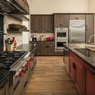 フェニックスの広いサンタフェスタイルのおしゃれなキッチン (アンダーカウンターシンク、レイズドパネル扉のキャビネット、茶色いキャビネット、御影石カウンター、茶色いキッチンパネル、レンガのキッチンパネル、シルバーの調理設備、セラミックタイルの床、茶色い床、茶色いキッチンカウンター) の写真