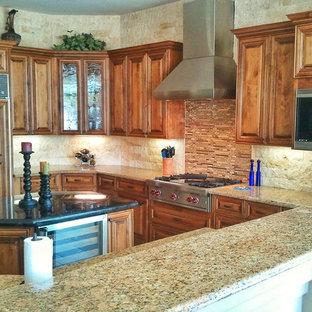 フェニックスの中サイズのトラディショナルスタイルのおしゃれなキッチン (アンダーカウンターシンク、レイズドパネル扉のキャビネット、中間色木目調キャビネット、御影石カウンター、ベージュキッチンパネル、石タイルのキッチンパネル、パネルと同色の調理設備、トラバーチンの床、ベージュの床、ベージュのキッチンカウンター) の写真