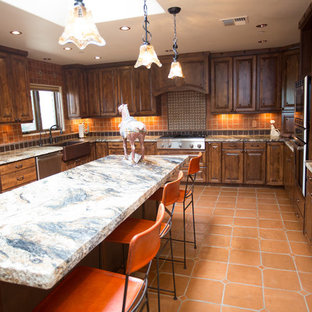 Large southwestern eat-in kitchen appliance - Example of a large southwest u-shaped terra-cotta floor and orange floor eat-in kitchen design in Phoenix with a farmhouse sink, raised-panel cabinets, distressed cabinets, granite countertops, multicolored backsplash, terra-cotta backsplash, paneled appliances and an island