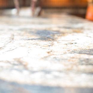 フェニックスの大きいサンタフェスタイルのおしゃれなキッチン (エプロンフロントシンク、レイズドパネル扉のキャビネット、ヴィンテージ仕上げキャビネット、御影石カウンター、マルチカラーのキッチンパネル、テラコッタタイルのキッチンパネル、パネルと同色の調理設備、テラコッタタイルの床、オレンジの床) の写真