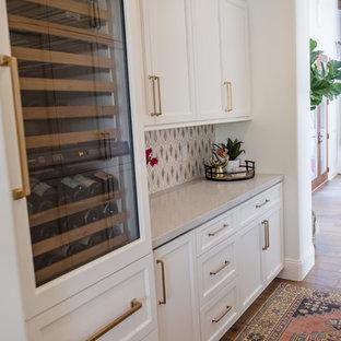 フェニックスの巨大なエクレクティックスタイルのおしゃれなキッチン (エプロンフロントシンク、落し込みパネル扉のキャビネット、白いキャビネット、珪岩カウンター、マルチカラーのキッチンパネル、モザイクタイルのキッチンパネル、シルバーの調理設備、無垢フローリング、グレーのキッチンカウンター) の写真