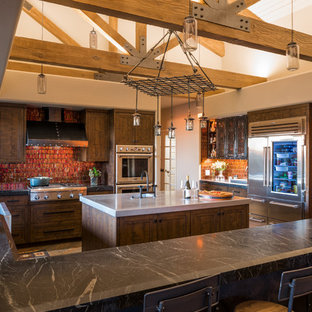 Contemporary kitchen appliance - Trendy u-shaped medium tone wood floor and brown floor kitchen photo in Phoenix with a farmhouse sink, recessed-panel cabinets, dark wood cabinets, red backsplash, mosaic tile backsplash, stainless steel appliances, an island and black countertops