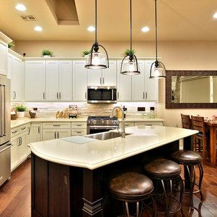 フェニックスの中くらいのサンタフェスタイルのおしゃれなキッチン (シングルシンク、シェーカースタイル扉のキャビネット、白いキャビネット、クオーツストーンカウンター、マルチカラーのキッチンパネル、石タイルのキッチンパネル、シルバーの調理設備、濃色無垢フローリング) の写真