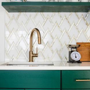 シアトルの小さい北欧スタイルのおしゃれなキッチン (アンダーカウンターシンク、シェーカースタイル扉のキャビネット、緑のキャビネット、クオーツストーンカウンター、白いキッチンパネル、大理石のキッチンパネル、シルバーの調理設備、ラミネートの床、アイランドなし、茶色い床) の写真