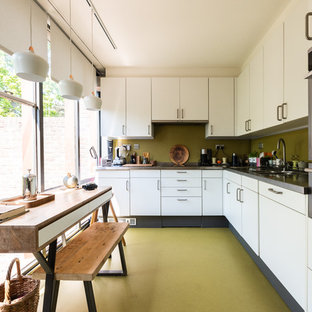 Medium sized midcentury l-shaped kitchen/diner in London with flat-panel cabinets, white cabinets, granite worktops, green splashback, stainless steel appliances, no island, green floors, black worktops and a double-bowl sink.