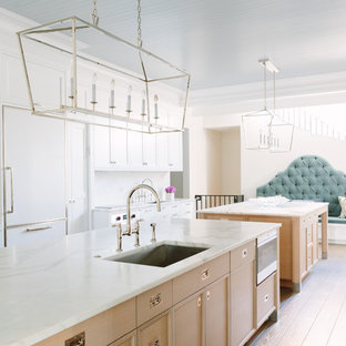 Large eclectic u-shaped eat-in kitchen in Chicago with an undermount sink, shaker cabinets, white cabinets, white splashback, panelled appliances, light hardwood floors, multiple islands, white benchtop, marble benchtops, marble splashback and beige floor.