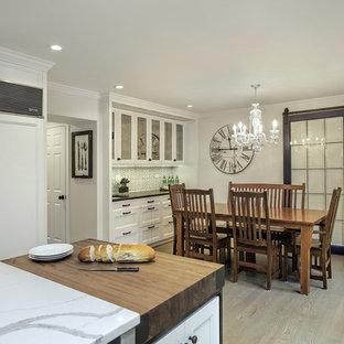 Imagen de cocina comedor de estilo de casa de campo con armarios con paneles empotrados, puertas de armario blancas, electrodomésticos con paneles, suelo de madera oscura, una isla y suelo marrón