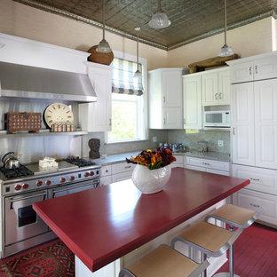 На фото: кухня в классическом стиле с фасадами с выступающей филенкой, белыми фасадами, серым фартуком, техникой из нержавеющей стали, деревянным полом, красным полом и красной столешницей