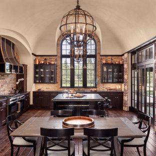 Diseño de cocina comedor en L, clásica, grande, con salpicadero beige, salpicadero de ladrillos, suelo de madera oscura, armarios con paneles empotrados, puertas de armario de madera en tonos medios, electrodomésticos negros y una isla