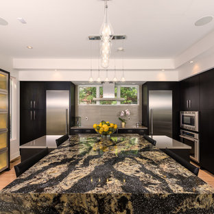 Contemporary eat-in kitchen ideas - Trendy l-shaped light wood floor eat-in kitchen photo in Indianapolis with flat-panel cabinets, black cabinets, gray backsplash, stainless steel appliances and two islands