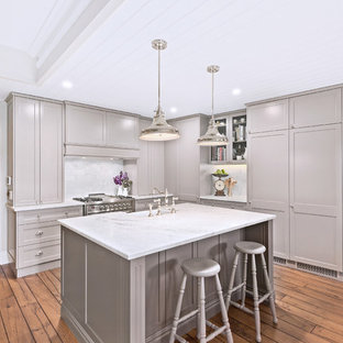 Transitional l-shaped kitchen in Sydney with a farmhouse sink, recessed-panel cabinets, grey cabinets, white splashback, stainless steel appliances, medium hardwood floors, with island, brown floor and white benchtop.