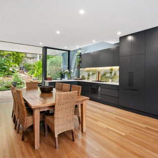 Photo of a contemporary l-shaped eat-in kitchen in Sydney with an undermount sink, black cabinets, quartz benchtops, green splashback, marble splashback, black appliances, medium hardwood floors, no island, white benchtop, flat-panel cabinets and brown floor.