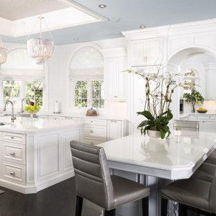 Idéer för att renovera ett stort vintage vit vitt kök med öppen planlösning, med en rustik diskho, luckor med upphöjd panel, vita skåp, bänkskiva i kvarts, vitt stänkskydd, stänkskydd i mosaik, integrerade vitvaror, mörkt trägolv, flera köksöar och brunt golv