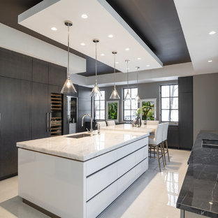 Design ideas for a large contemporary u-shaped separate kitchen in Toronto with flat-panel cabinets, quartzite benchtops, porcelain floors, with island, white floor, a single-bowl sink, white cabinets, white splashback, stone slab splashback, stainless steel appliances and white benchtop.