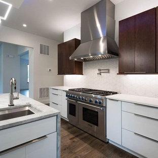 ワシントンD.C.の広いコンテンポラリースタイルのおしゃれなキッチン (アンダーカウンターシンク、フラットパネル扉のキャビネット、ターコイズのキャビネット、クオーツストーンカウンター、白いキッチンパネル、セラミックタイルのキッチンパネル、シルバーの調理設備、濃色無垢フローリング、茶色い床、白いキッチンカウンター) の写真