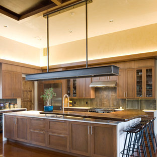 Photo of an expansive rustic l-shaped kitchen/diner in Albuquerque with shaker cabinets, dark wood cabinets, wood worktops, multi-coloured splashback, stainless steel appliances, a submerged sink, stone tiled splashback, concrete flooring and an island.
