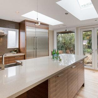 Foto di una cucina design di medie dimensioni con lavello da incasso, ante lisce, ante marroni, paraspruzzi grigio, paraspruzzi con piastrelle di vetro, elettrodomestici in acciaio inossidabile, parquet chiaro e isola