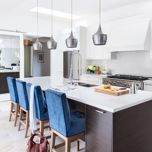 Design ideas for a mid-sized contemporary single-wall eat-in kitchen in Vancouver with a double-bowl sink, shaker cabinets, white cabinets, white splashback, stainless steel appliances, solid surface benchtops, with island, multi-coloured floor and white benchtop.